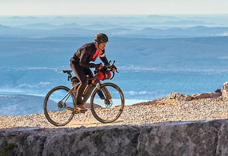 Man biking up a rocky hill