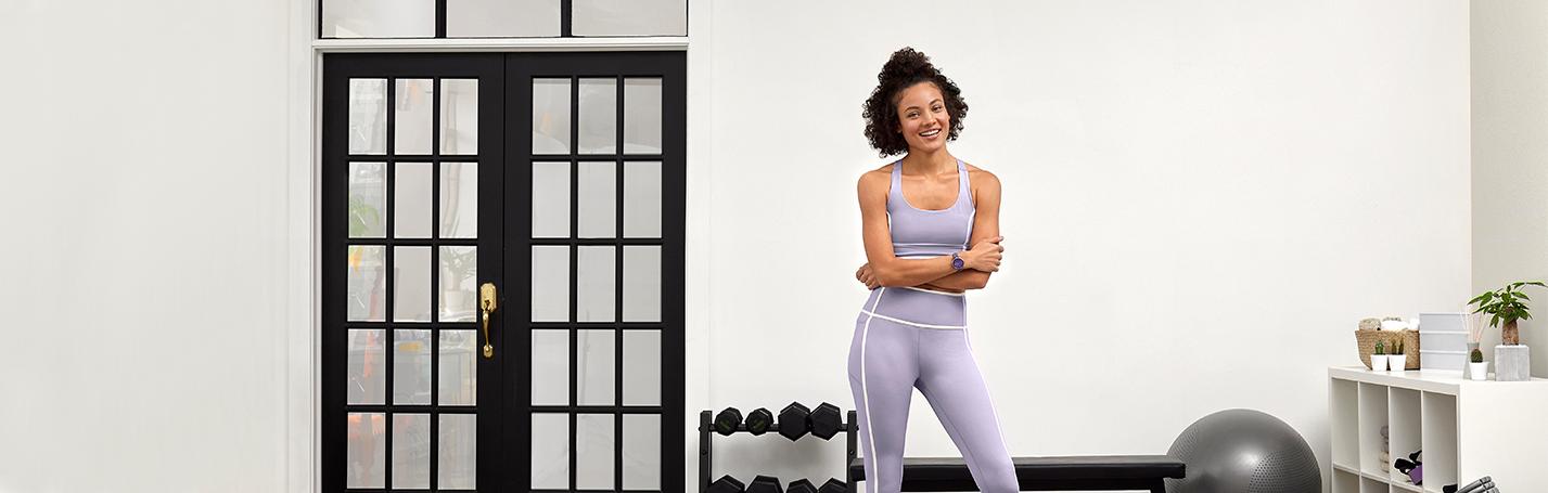 Woman in home gym wearing a Garmin smartwatch.