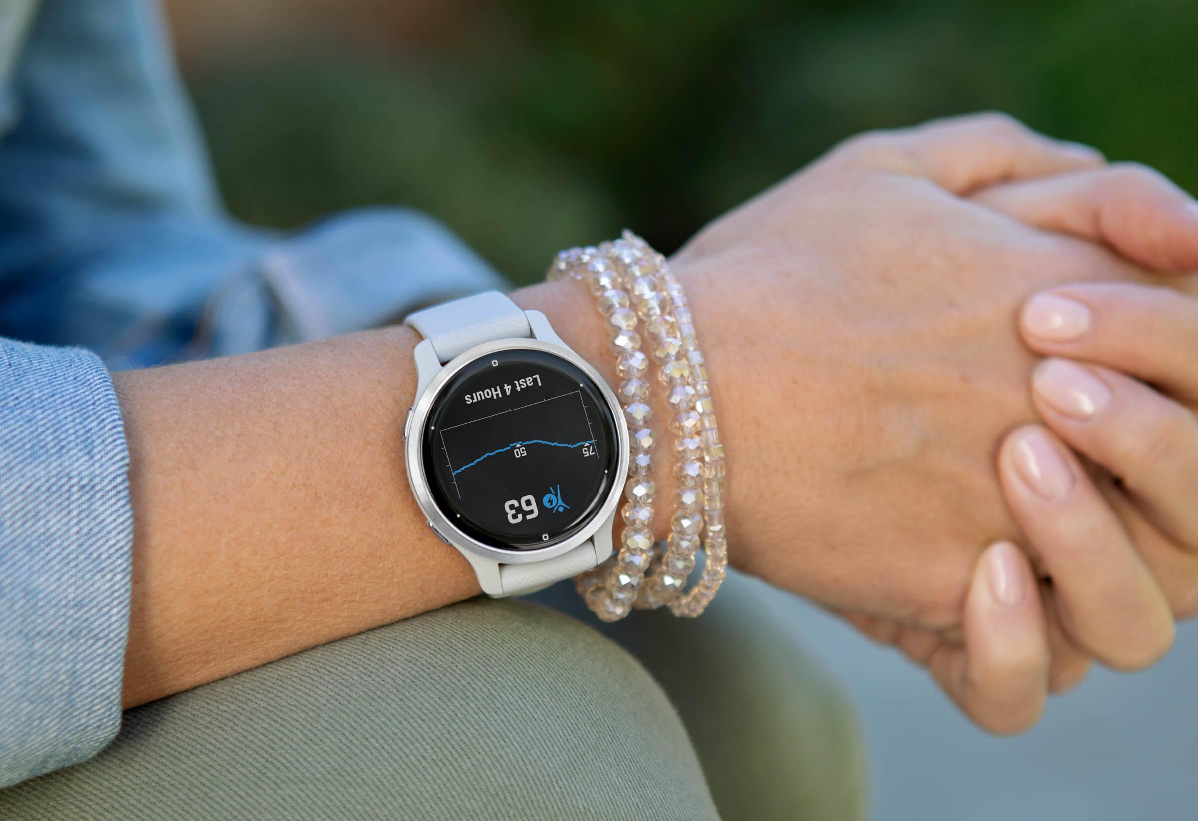Woman wearing Garmin smartwatch to measure body battery for high-intensity fitness workouts.
